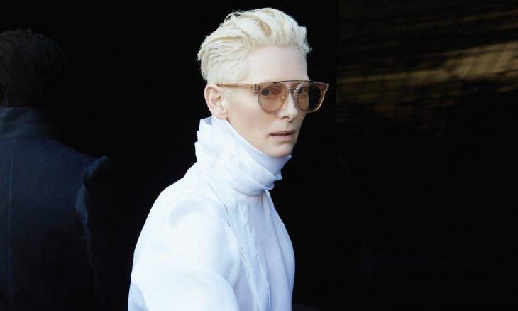 Mujer de cabello blanco, lentes de sol y abrigo blanco