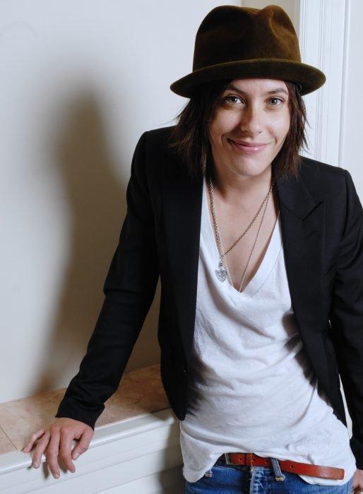 Mujer sonriendo con sombrero, blusa blanca y saco