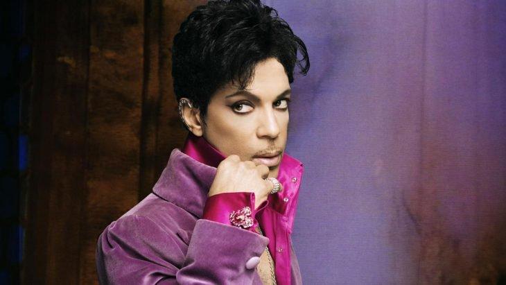 Hombre con ojos delineados y traje púrpura con rosa
