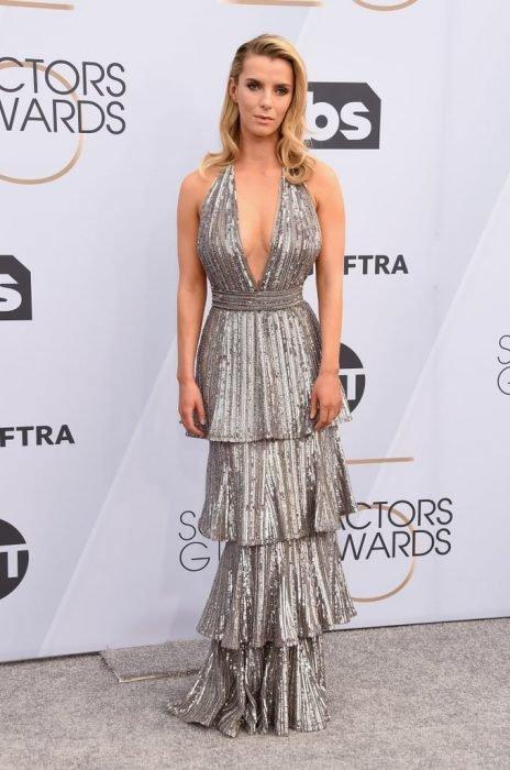 Betty Gilpin en los SAG Awards 2019 con un vestido en capas plateado es considerada una de las peores vestidas