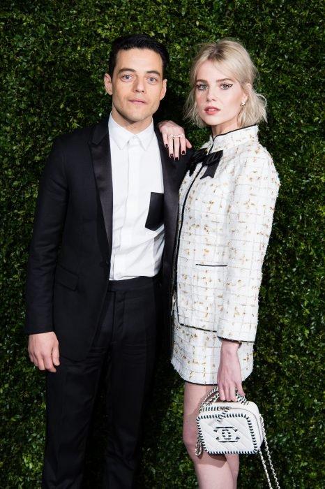 Rami Malek y Lucy Boynton abrazados posando para una foto durante la alfombra roja de la pasarela de Chanel