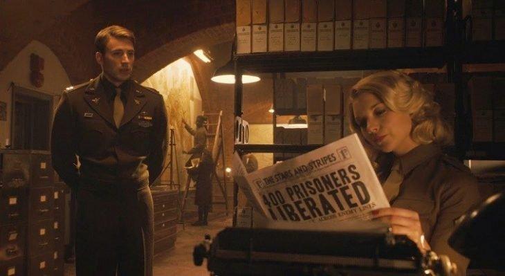 Chica sentada en un escritorio leyendo el periódico, mientras un hombre la observa fijamente, escena de la película Capitán América: el primer vengador, Natalie Dormer, Chris Evans