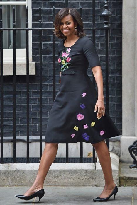 Michelle Obama sonriendo y caminando por la avenida