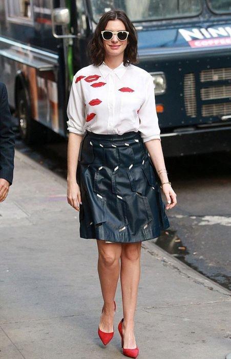 Anne Hathaway sonriendo y posando para una foto en plena avenida