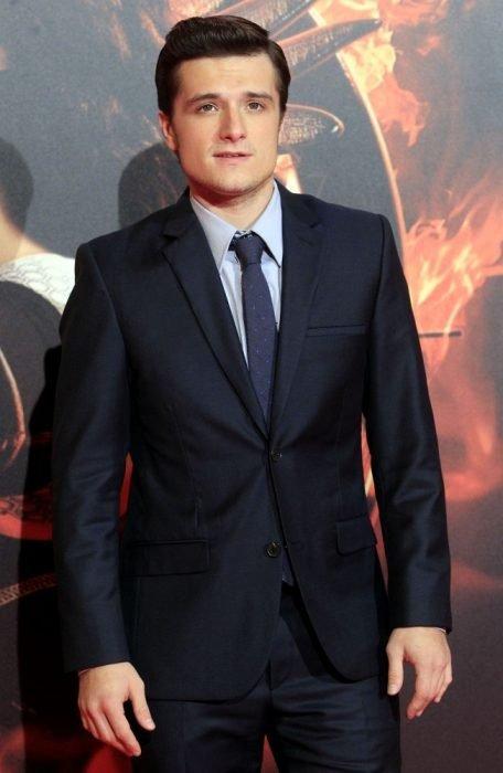 Chico bien peinado visitneod un traje sastre negro con corbata azul