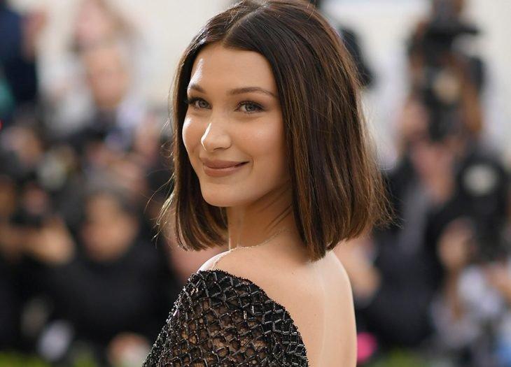 Chica de cabello corto, castaño y lacio con un vestido negro