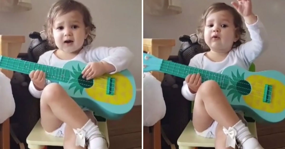 toddler playing fake guitar.jpg?resize=412,232 - Toddler Acts Like A Rockstar While Playing A Toy Guitar