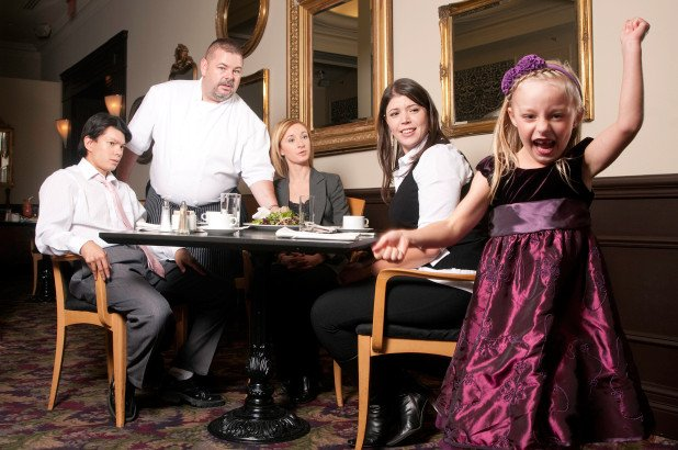 A little girl is acting up in a restaurant while diners look on