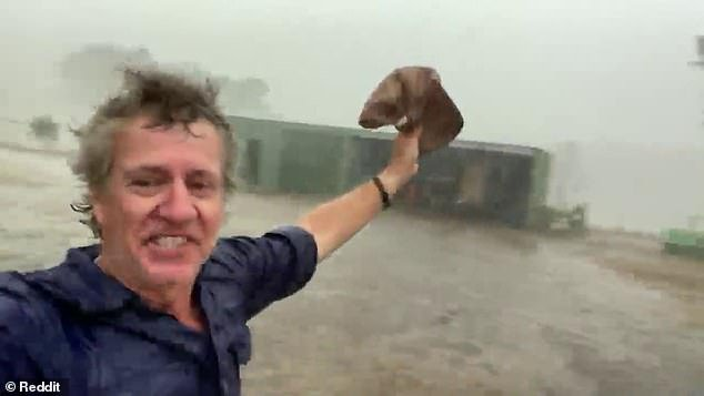 The overjoyed farmer is welcoming the rain on his farm in New South Wales following months of drought