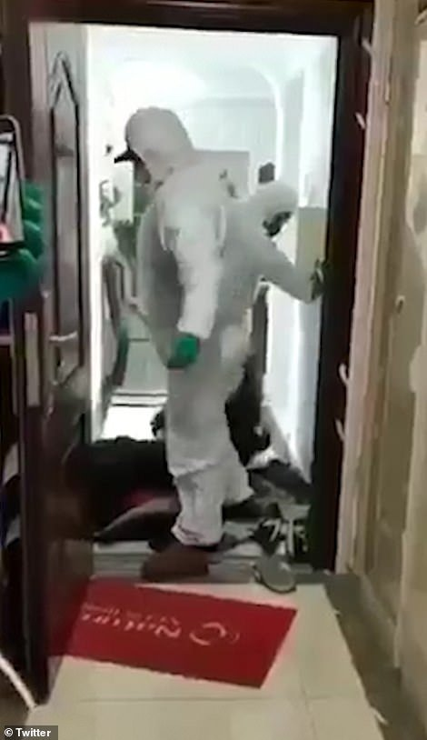 The footage, thought to have been filmed in Wuhan, China, shows officials in protective suits forcefully removing people suspected of having coronavirus from their home