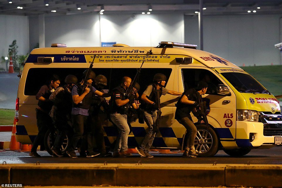 Thailand security forces take cover behind an ambulance as they chase a shooter hidden in a shopping mall after a mass shooting in front of the Terminal 21, in Nakhon Ratchasima, Thailand today
