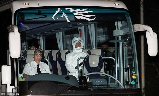 A medical worker wearing a full hazmat suit can be seen in the bus next to a driver - wearing no protective gear - while the British evacuees from Wuhan sit in the back