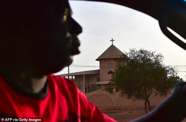 A man drives past a church in the city of Ouahigouya, northern Bukina Faso, on October 30, 2018