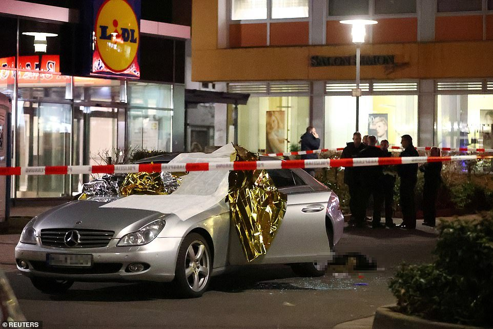 A Mercedes Benz was left damaged with glass covering the floor as police look on at the crime scene in Hanau last night