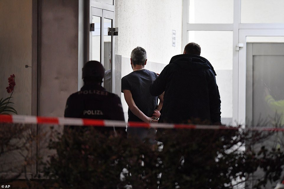 Police handcuff a man near the scene of a shooting in Hanau, Germany early on Thursday morning