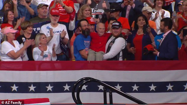 The heartwarming video shared on Twitter shows two men--one wearing a Trump hat--carrying the elderly man down a flight of stairs and across Arizona Veterans Memorial Coliseum as crowds cheered and chanted