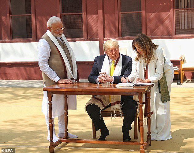 Melania Trump, in a prayer shawl and slippers, sins the guest book at Gandhi