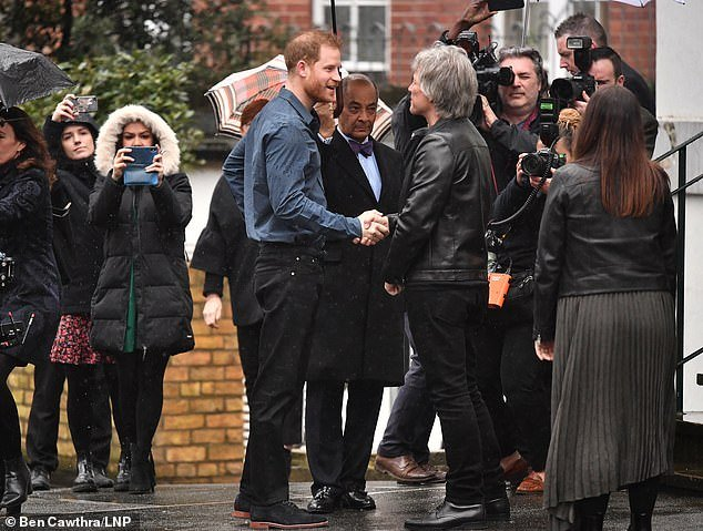Harry shakes hands with Jon Bon Jovi Abbey Road studios this morning before recording a duet