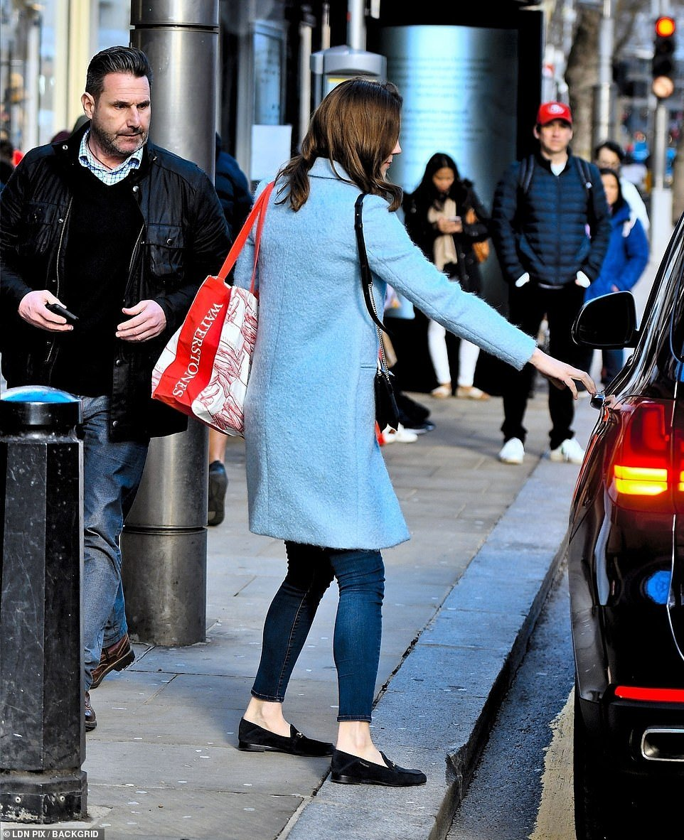The Duchess was seen opening her own car door as she stepped off the busy pavement with the Waterstones-branded bag slung over her shoulder