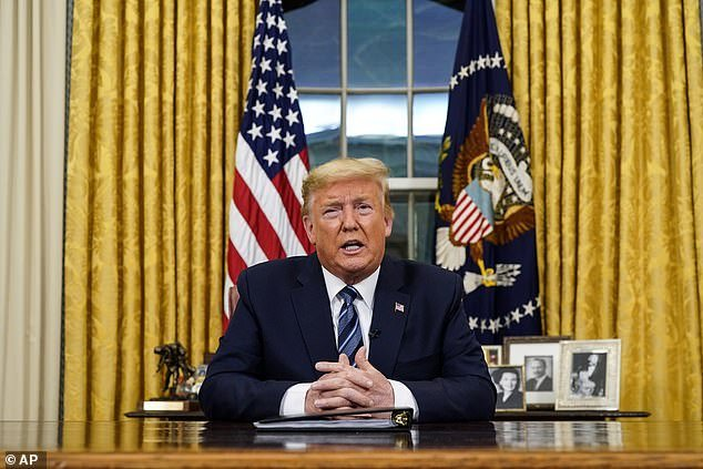 Power of the office: Donald Trump spoke from behind the Resolute desk, in front of the United States flag, the presidential seal, and pictures of (from left) his mother Mary Anne, father Fred, and a picture of himself with a young Ivanka on his lap