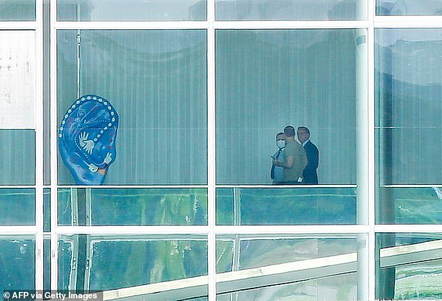 Brazilian President Jair Bolsonaro is pictured with his son Eduardo Bolsonaro (center) and an adviser, inside Alvorada Palace in Brasilia
