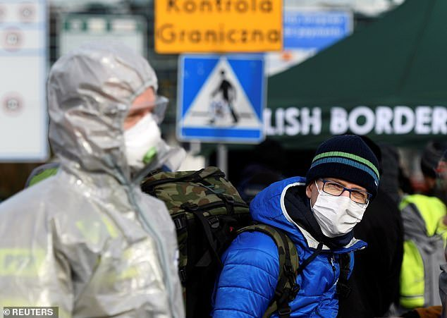 A man wearing a face mask stands on the Poland-German border crossing point on Sunday