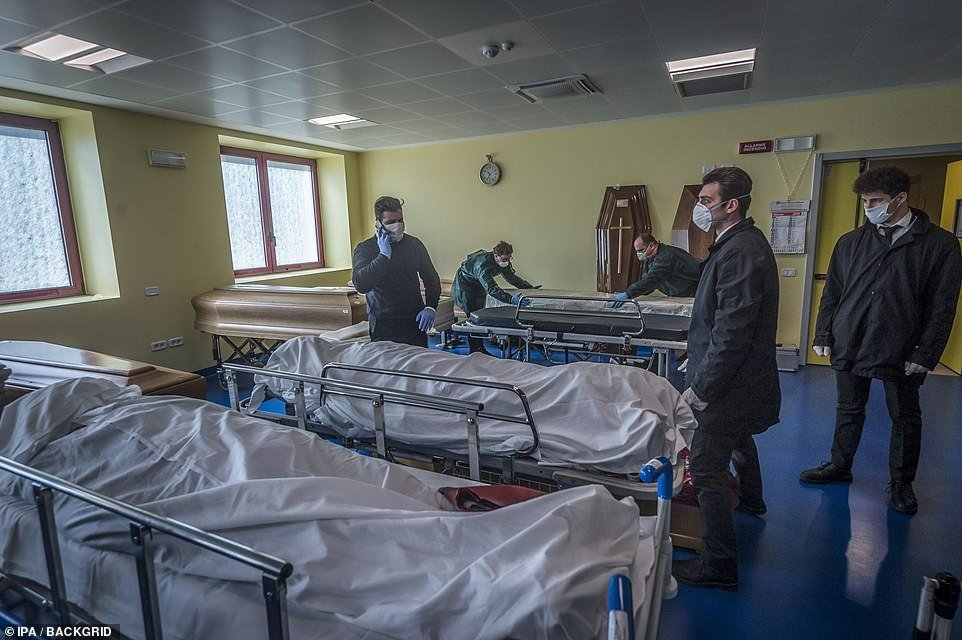 Hospital workers in face masks stand over trolleys at the Ponte San Pietro hospital in Bergamo on Tuesday as they prepare coffins