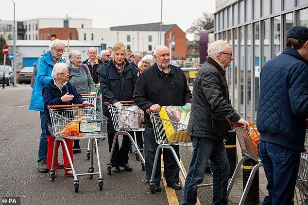 Older customers queue outside a Sainsbury