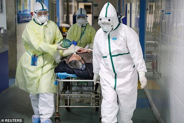 Medical workers in protective suits move a patient at an isolated ward of a hospital in Caidian district following an outbreak of the coronavirus in Wuhan, China