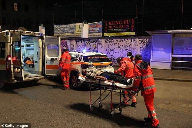 Pictured: Medical staff carry away man who was lying unconscious on the ground in Rome, Italy, as the country continues its nationwide lockdown