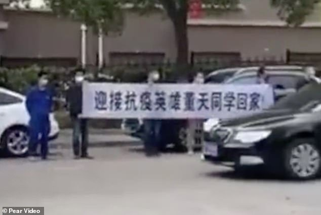 People are seen holding a banner that reads