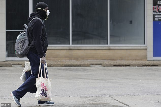 Illinois is under a stay-at-home order, with all non-essential business and travel banned. A pedestrian is seen above carrying shopping bags in Chicago on Saturday