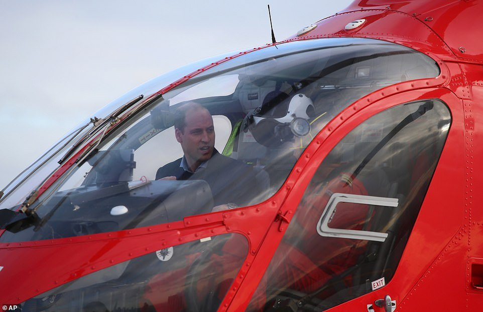 Prince William is pictured arriving on the Royal London Hospital rooftop aboard a London Air Ambulance helicopter, in London in January last year