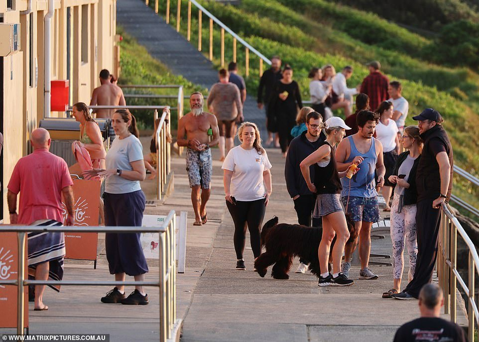 Walkers stand outside a cafe - which is only allowed to serve takeaway food and drinks - on the Northern Beaches on Friday