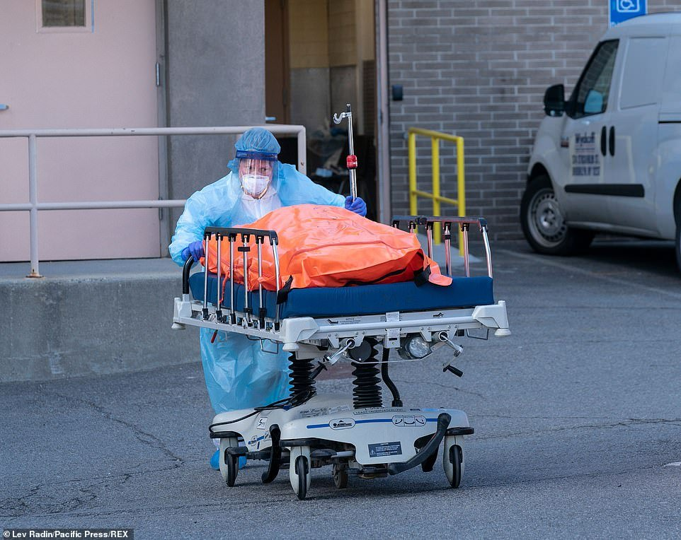 The body of deceased patient in orange body bag is moved from the hospital to a refrigerator truck serving as temporary morgue outside of Wyckoff Heights Medical Center in Brooklyn