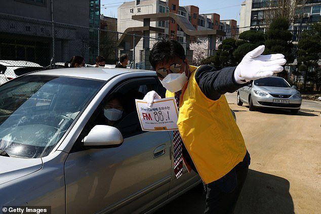 Fifty-one people who recovered from coronavirus in South Korea have tested positive again – raising fears the virus can be reactivated. Pictured: A church worker directs people to a drive-through worship inSeoul
