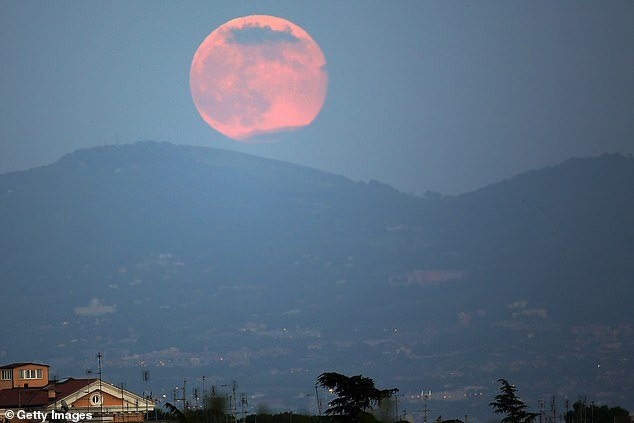 Dust off your binoculars, earmark a comfortable perch next to an east-facing window, set your alarm clock and prepare for a front row seat to witness a true natural wonder of the world. A pink full moon is pictured above in Rome in 2013