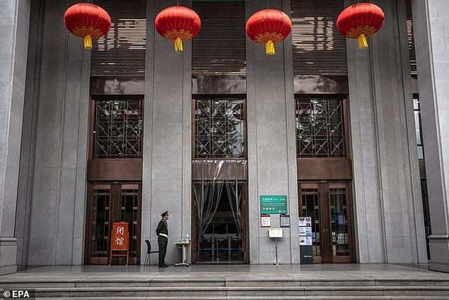 A security man stands guard next to a library of Wuhan University, in Wuhan, China