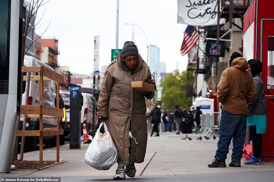 A woman pictured leaving the Mission with her Easter lunch in hand on Sunday afternoon as she walks through Manhattan