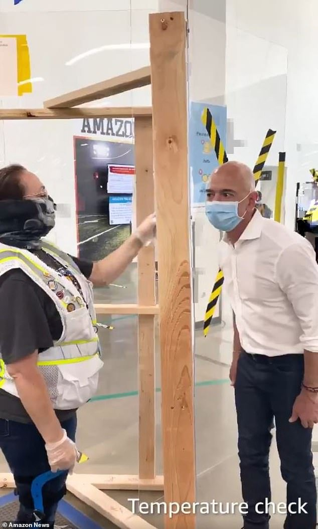 The economic damage for most has been widespread and severe amid COVID-19 But under lockdowns Amazon has seen a surge in demand for online orders. Bezos is pictured wearing a mask and having a temperature check at a facility in Dallas last week where an employee later tested positive