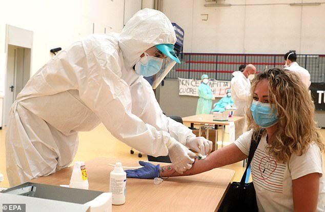 A woman undergoes a serological test during the coronavirus lockdown in Milan on Tuesday