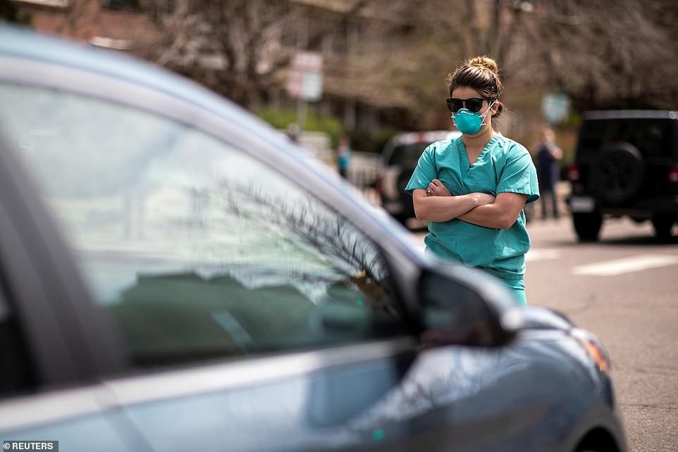 You shall not pass: A group of healthcare workers stood in the street to counter-protest the calls for re-opening, silently obstructing cars as they drove down towards the Capitol, dressed in scrubs and facemasks