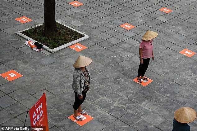 In this file photo taken on April 11, 2020, residents wearing face masks practice social distancing as they wait in a queue for free rice, amid Vietnam