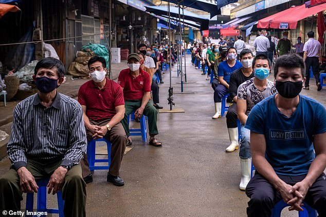 Vendors and labourers from Long Bien market wear face masks and queue in safe distance to take the coronavirus disease (COVID-19) rapid test  last week in Hanoi, Vietnam