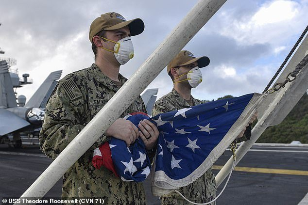 92 percent of the personnel on board have been tested for the virus.3,872 tests have come back negative. Pictured: Crew members prepare to raise the flag on the USS Roosevelt
