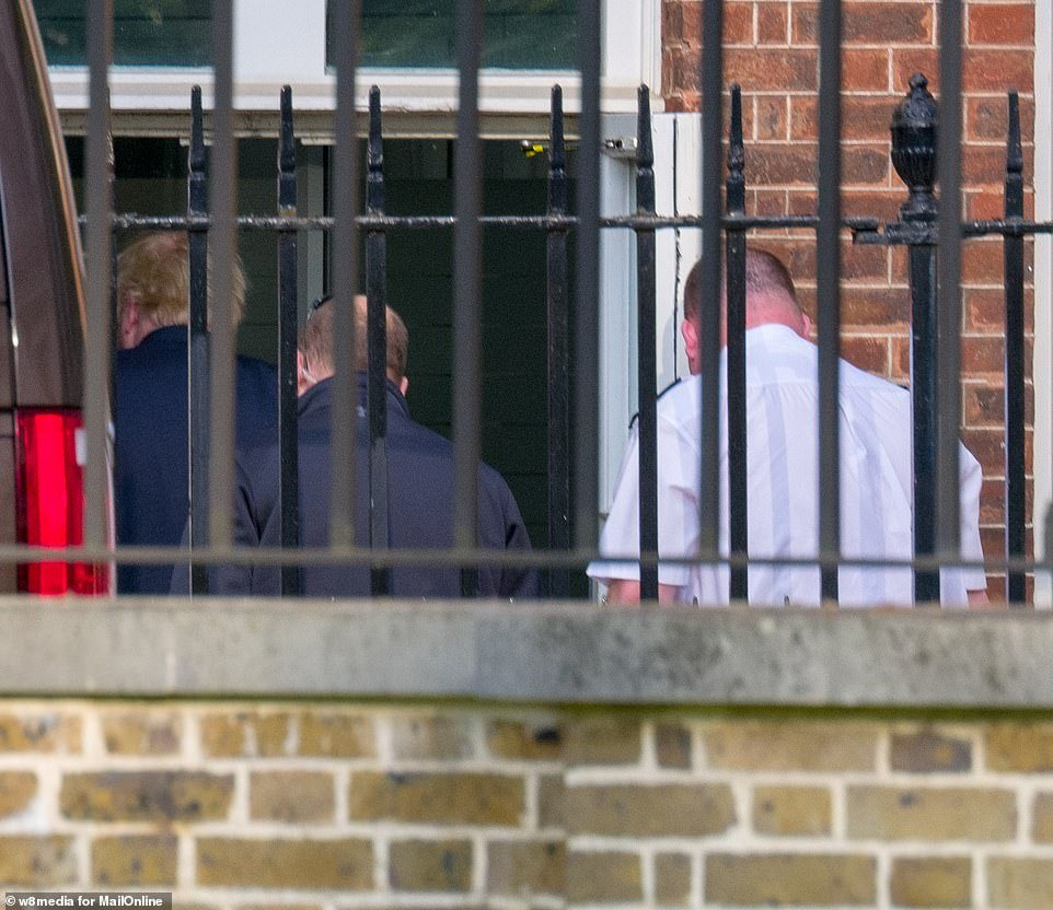 Mr Johnson was flanked by his security detail as he headed into the rear entrance of Downing Street
