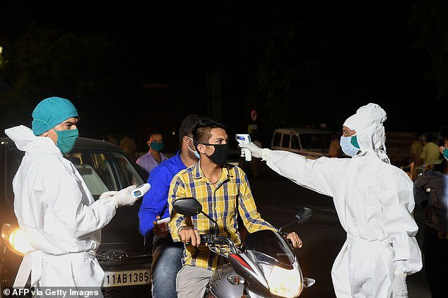 It is unclear from reports which of the two tests was shown to have such a low accuracy rate. Pictured: A health worker checks the body temperature of the rider of a moped in India