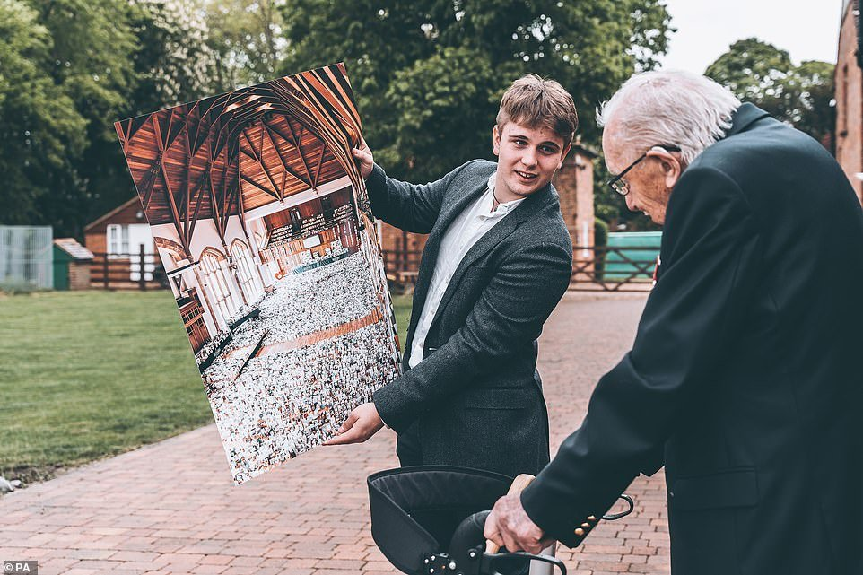 Benjie Ingram-Moore, 16, presenting his grandfather Captain Tom Moore with a photograph of the Great Hall of Bedford School, Bedfordshire, filled with cards for his 100th birthday