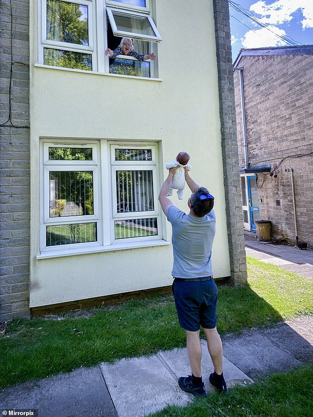 Joan Cartwright, 92, flung her arms out through the open window of her flat in Horsforth, Leeds as Will, 36, stood in the garden below and held up his baby Holly so Joan could see her
