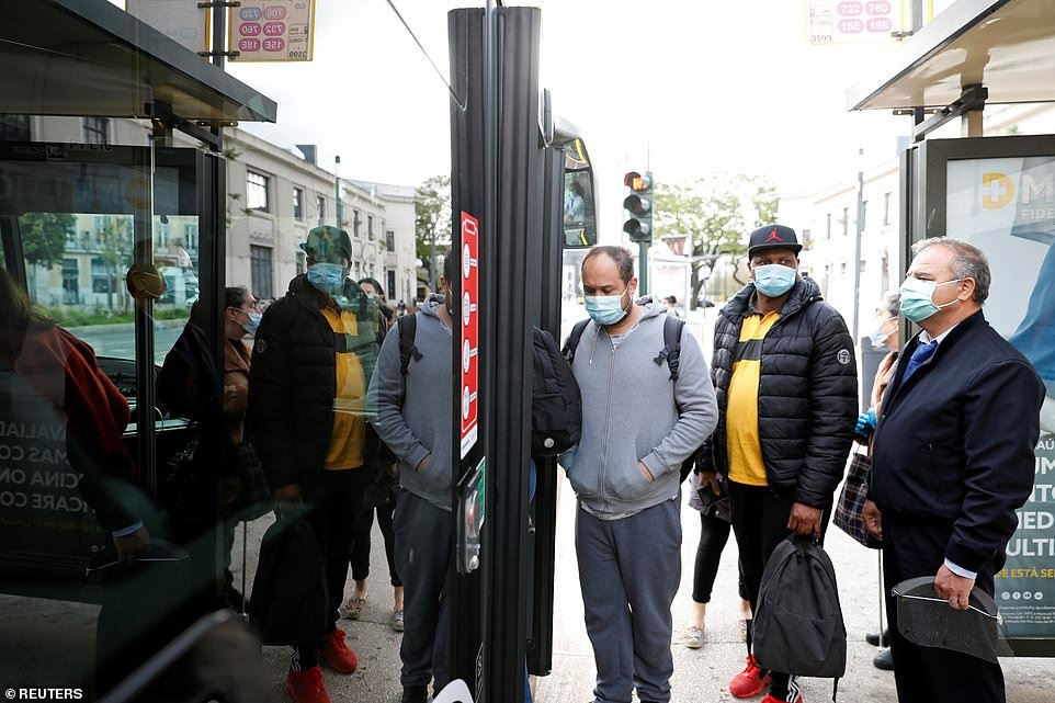 PORTUGAL: People wearing protective masks board a bus at Cais do Sodre station in Lisbon this morning, as Portugal begins to ease its own coronavirus lockdown